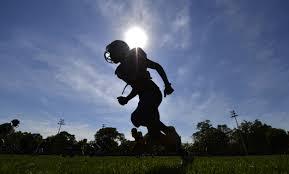 Football Player battles heat on synthetic turf